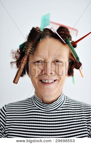 Senior female multitasking with many combs in hair
