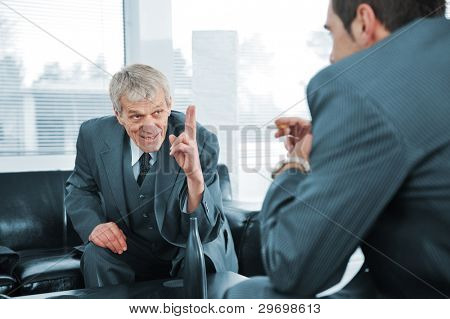 Senior boss giving orders to young colleague at break in office, relaxed meeting