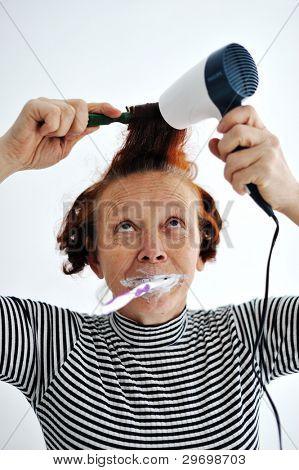 Senior woman brushing teeth and drying hair