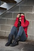 picture of child abuse  - Teenage girl sitting against brick wall in a depressed state - JPG