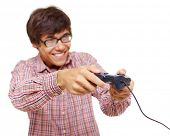 Happy young man in glasses playing video game with joystick over isolated background, focus on joyst
