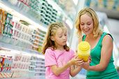 image of grocery-shopping  - woman and girl choosing produces in dairy shopping mall - JPG