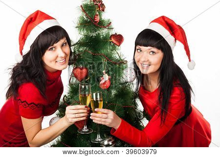 Two girls with champaigne near Christmas tree