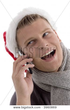 Smiling Male With Christmas Hat Talking On Cell Phone