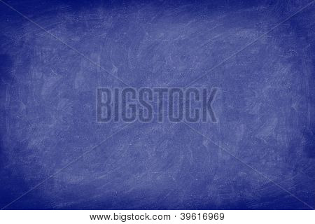Chalkboard / dark blue blackboard texture background. Used feel, textured with chalk traces. Photo.