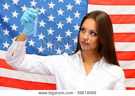 Portrait of female doctor or scientist showing and analyzing liquid in flask over American Flag background