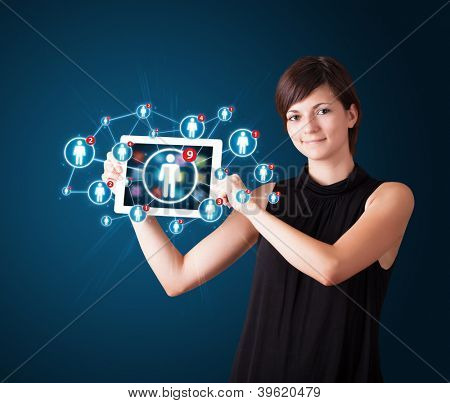 Beautiful young woman holding tablet with social network icons