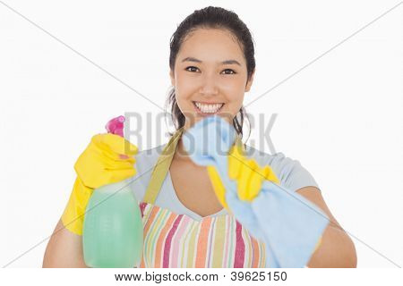Smiling woman in apron and gloves wiping in front of her