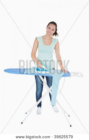Smiling woman ironing jumper on an ironing table on a white background