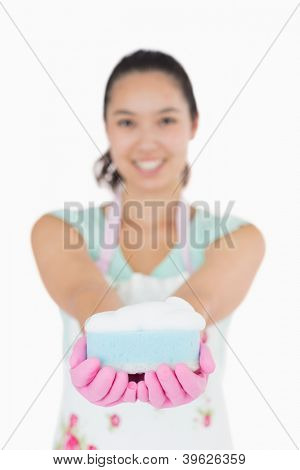 Beautiful woman holding a cleaning sponge with both hands on a white background