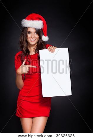 Traditional woman Christmas Santa holding a blank sign, showing something by her index finger.