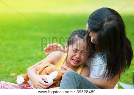 Mother is comforting her crying daughter