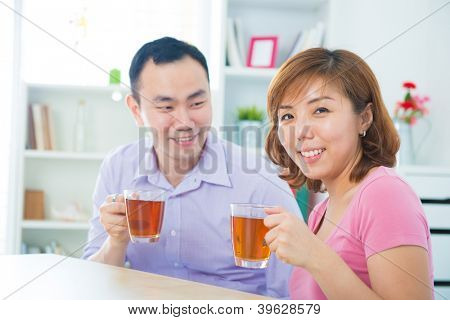 Attractive asian couple enjoying tea/coffee at home