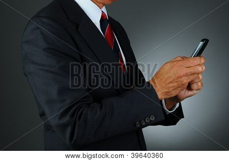 Closeup of a businessman in a dark suit against a light to dark gray background using his cell phone to send a text. Man is unrecognizable and seen from the side.