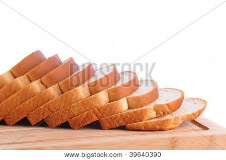 Closeup of a loaf of white bread on a wood cutting board. Slices of bread are fanned out. Horizontal format over a white background.