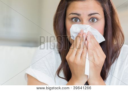 Brunette sneezing into tissue