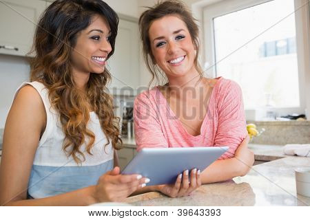 Happy friends using tablet computer having coffee in kitchen
