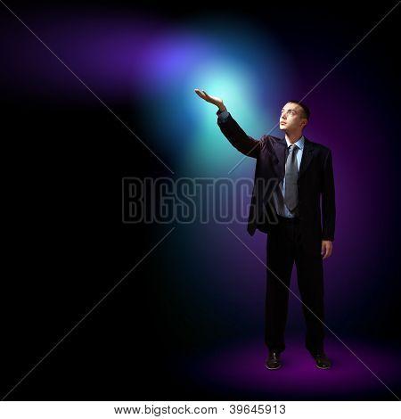 Junger erfolgreicher Geschäftsmann hält ein strahlendes Licht in der Hand als Symbol für Erfolg und advancem