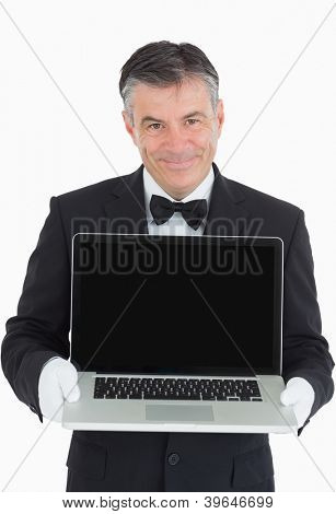 Smiling waiter showing us something on a laptop in front of camera