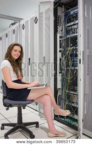Happy woman with laptop working with servers in data center