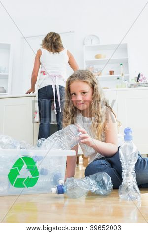 Daughter sorting plastics while her mother cleaning kitchen