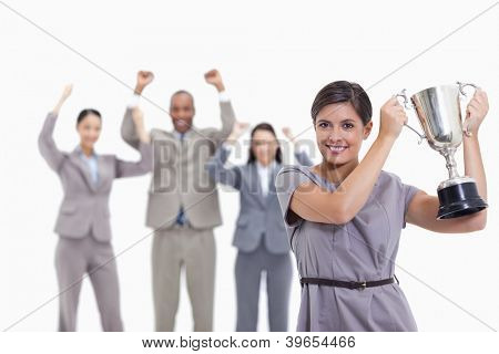 Close-up of a woman smiling and holding up a cup with co-workers raising their arms in the background