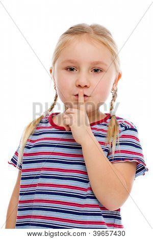 Little girl showing silence sign. Studio shot.
