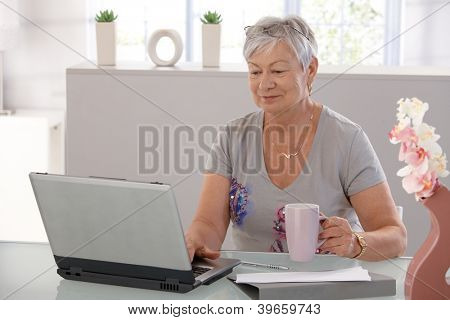 Elderly woman working on laptop computer, smiling, drinking tea.