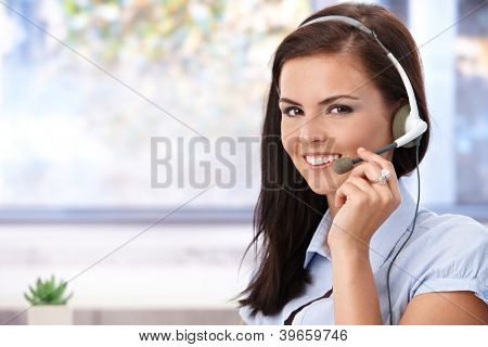 Portrait of pretty young dispatcher smiling, looking at camera.