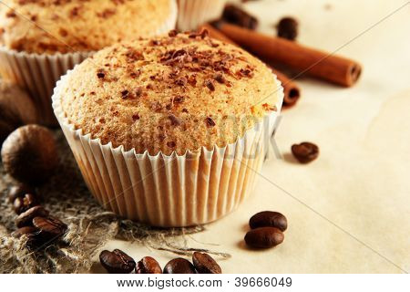 tasty muffin cakes with chocolate, spices and coffee seeds, on beige background