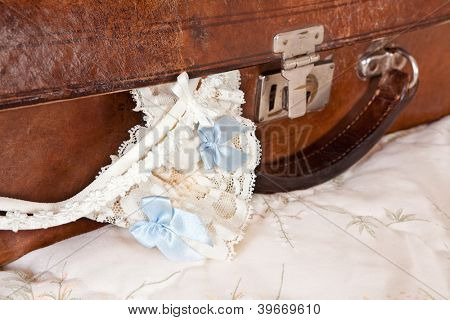 Wedding garter and bra straps hanging out of a vintage suitcase