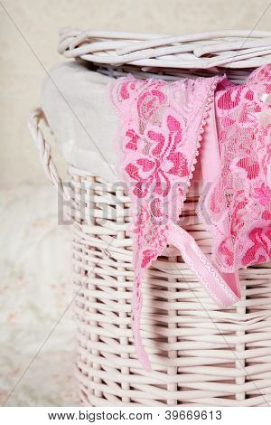 Pink lace bra and thong in a vintage wicker laundry basket