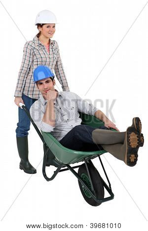 craftswoman carrying a craftsman sitting in a wheelbarrow