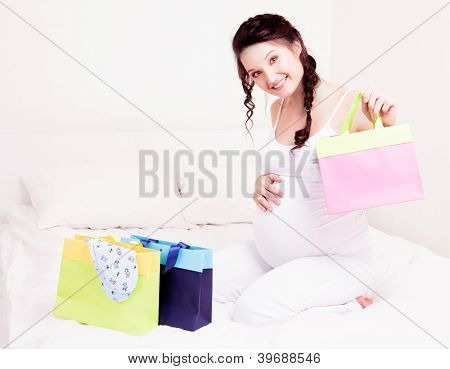 beautiful young pregnant woman with shopping bags and baby's clothes in bed at home