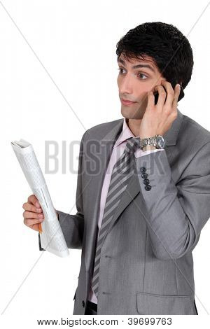 Businessman taking on phone and holding newspaper
