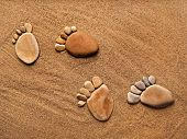 stock photo of footprints sand  - trace feet steps made of a pebble stone on the sea sand backdrop - JPG