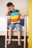 stock photo of bunk-bed  - Sleepy little boy sitting on bunk bed - JPG