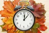 Retro alarm clock on autumn leaves. Time change concept.