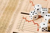 stock photo of stock market crash  - Dice and stock market charts in the newspaper - JPG