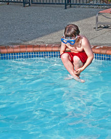 image of cannon-ball  - This 8 year old Caucasian boy is wearing a swimming mask while doing a cannon ball mid air into a pool of water - JPG