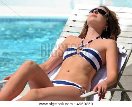 Girl Sunbathing By The Pool