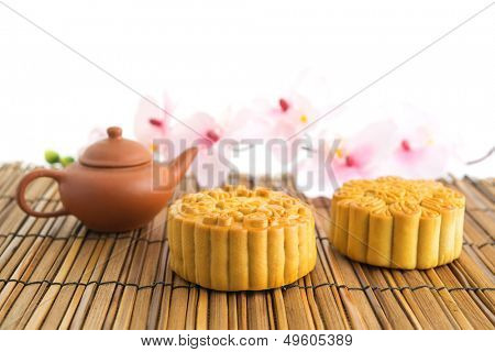 Traditional mooncakes with teapot. Chinese mid autumn festival foods. The Chinese words on the mooncakes means assorted fruits nuts and durian pure lotus paste, not a logo or trademark.