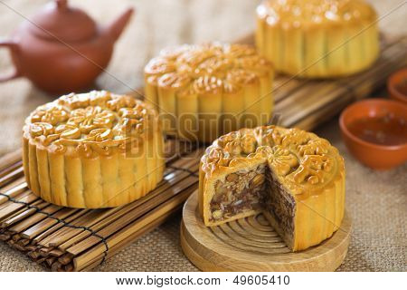 Chinese mid autumn festival foods. Traditional mooncakes on table setting.  The Chinese words on the mooncakes means assorted fruits nuts, not a logo or trademark.