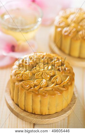 Chinese mid autumn festival foods. Traditional mooncakes on table setting with flower tea.  The Chinese words on the mooncakes means assorted fruits nuts, not a logo or trademark.