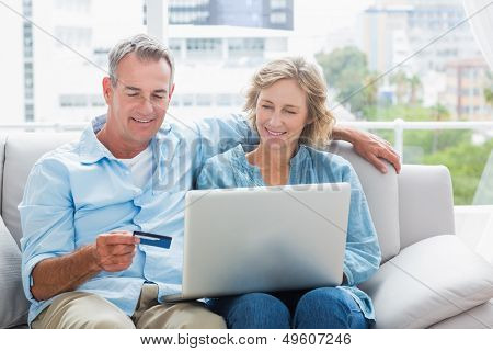 Smiling couple sitting on their couch using the laptop to buy online at home in the sitting room