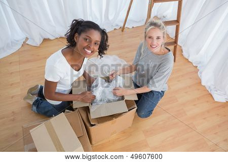 Happy housemates unpacking boxes in new home and smiling at camera