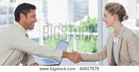 Blond businesswoman having an interview in office and shaking hands with interviewer