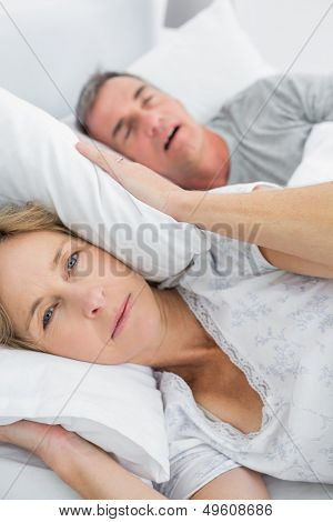 Tired wife blocking her ears from noise of husband snoring looking at camera in bedroom at home