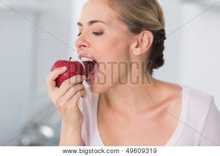 Pretty woman in her kitchen munching apple