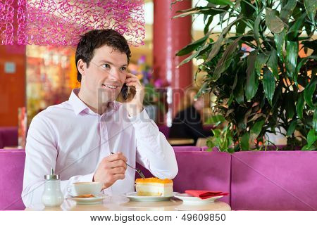 Young man in a cafe or ice cream parlor eating a cake and using his phone, maybe he is single or waiting for someone